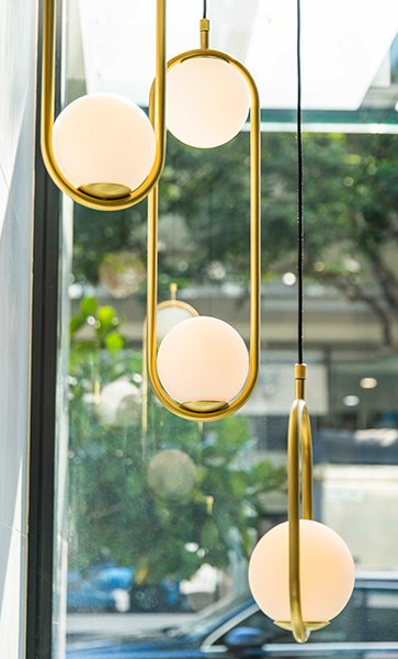 Hanging spherical lamps pictured in front of a window looking onto a street