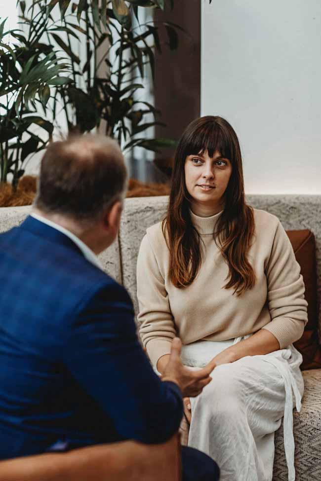 VSON laser eye surgery clinic eye specialist talking to woman sat on sofa listening