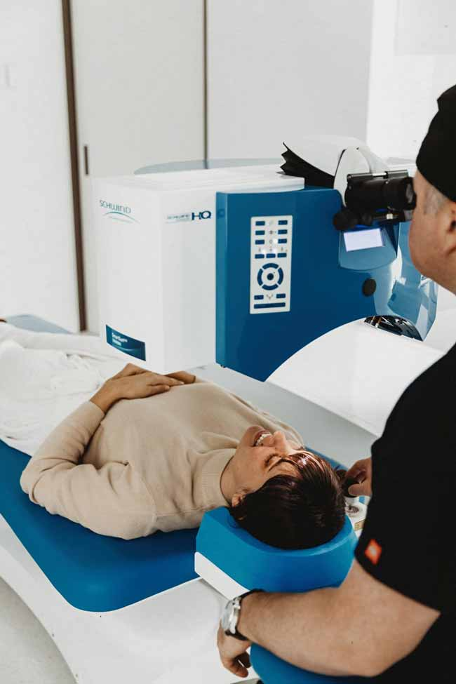 Ophthalmologist in VSON laser eye surgery clinic looking into Schwind eye laser system, assessing a patient lying on the bed