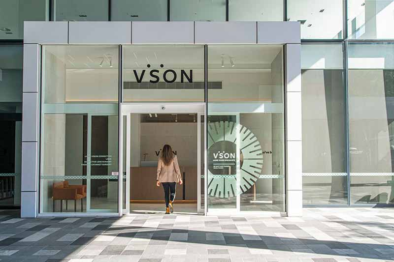 Woman in blaser jacket viewed from behind entering the VSON laser eye surgery clinic in Brisbane